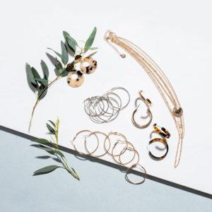Kultainen kaulakoru, rengaskorvakorusetti kullan- ja hopeanvärisenä, kultaiset rengaskorvakorut, ruskeat kilpikonnakuvioidut renkaat ja nudet kilpikonnakuvioidut riipuskorvakorut.
