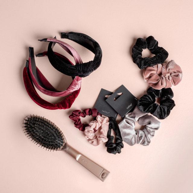 Eri väriset, trendikkäät hiuspannat ja hiusdonitsit sekä luonnonharjas-hiusharja.