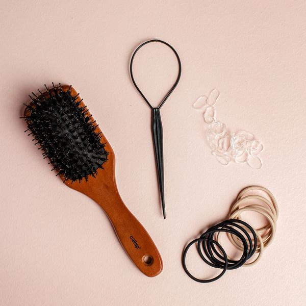 Cailap puinen hiusharja, hiuslasso, silikonihiuslenkit sekä mustia ja vaaleita hiuslenkkejä.